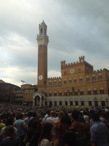 "Crowds awaiting the ""estrazione delle contrade"" or the drawing of the contrade that will run the next Palio. The drawn contrada's flags get hung out the windows of the Palazzo Pubblico in front of the waiting crowd."